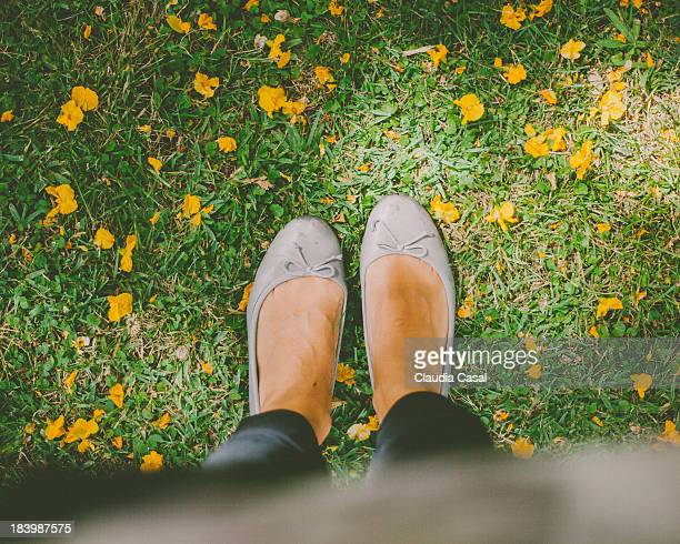 Girl feet on grass ground with yellow flowers