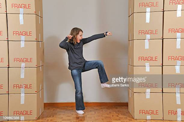 Girl fighting a wall of cardboard boxes