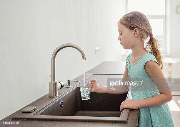 Girl filling up a glass of water in the kitchen