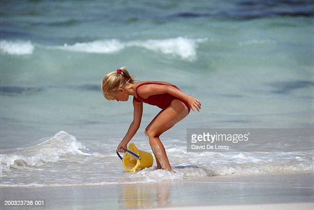 girl (6-7) filling water in bucket on beach, side view - little girls bent over stock photos and pictures