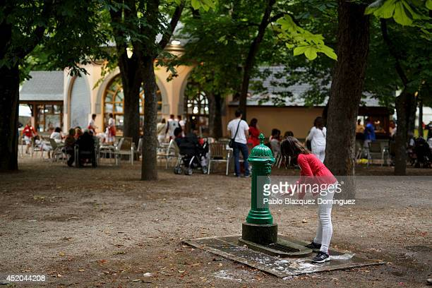 A girl fills a glass of water at a public fountain during the sixth day of the San Fermin Running Of The Bulls festival on July 11 2014 in Pamplona...