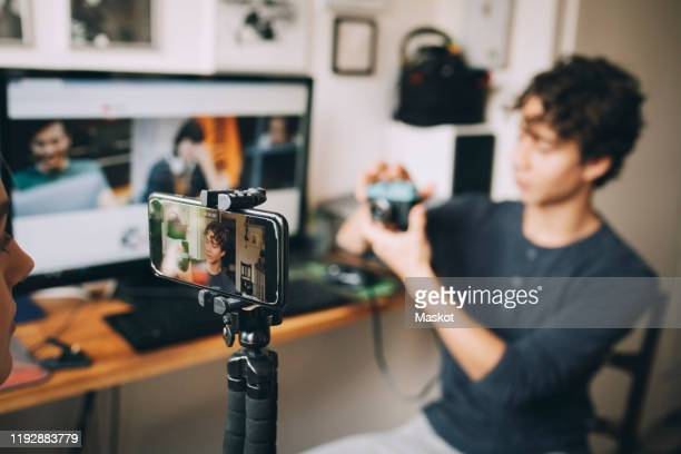 girl filming friend on mobile phone using camera while sitting at home - influencer stock pictures, royalty-free photos & images