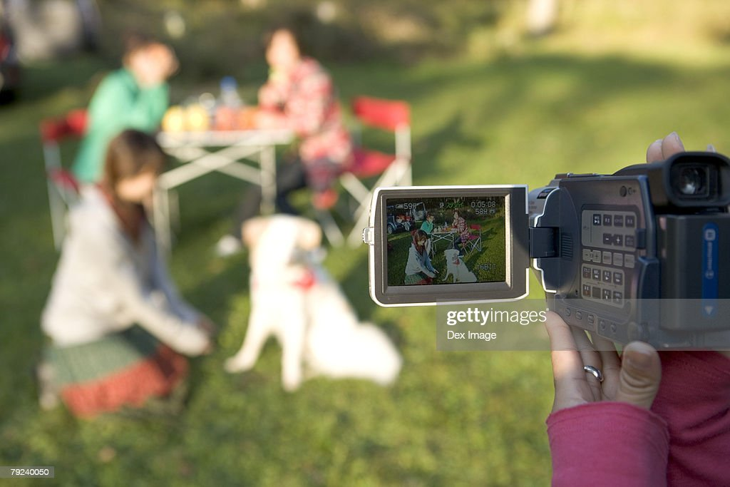 A girl filming with a digital camera : Stock Photo