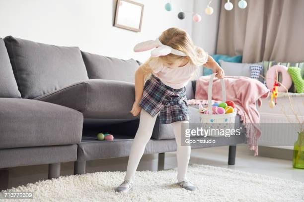 girl finding easter eggs under sofa cushion - under skirt stock photos and pictures