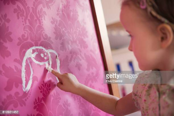 girl finger painting a rabbit shape onto pink wallpaper - 4 girls finger painting stock photos and pictures