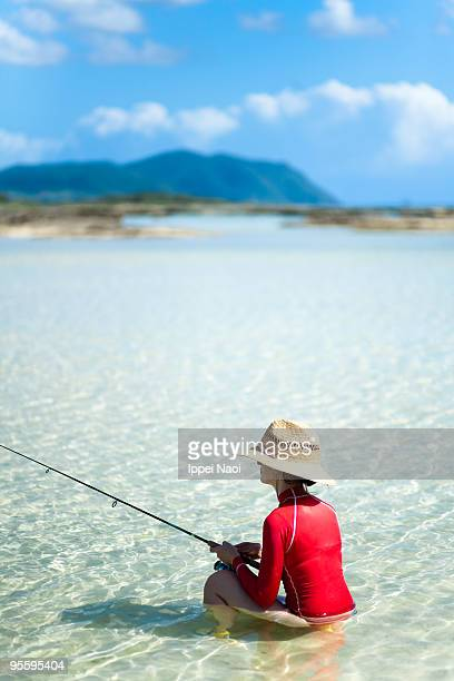 Girl fishing in clear tropical waters, Okinawa