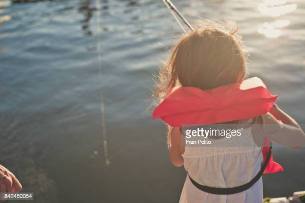 Girl fishing on a pier.