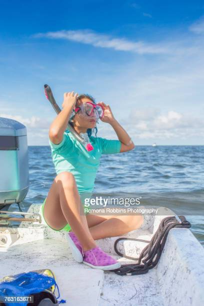 Girl fitting on diving mask on boat