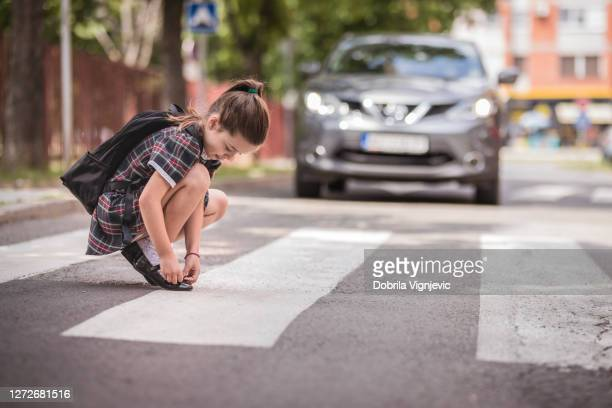 girl fixing her shoeson at the crosswalk - pedestrian stock pictures, royalty-free photos & images