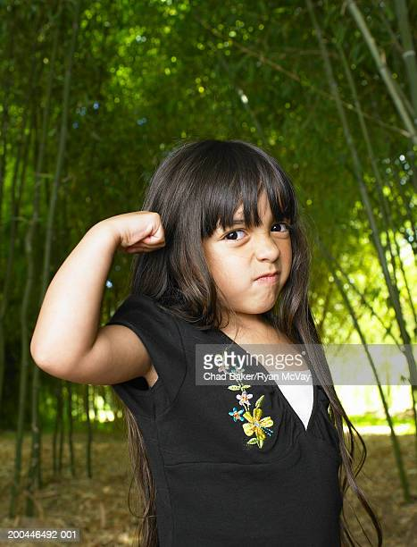 Girl (4-6) flexing muscles in bamboo grove, portrait