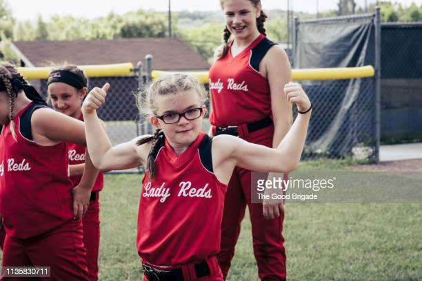 girl flexing muscles on softball field - softball sport stock pictures, royalty-free photos & images