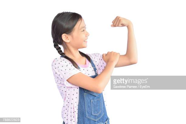 Girl Flexing Muscles While Standing Against White Background