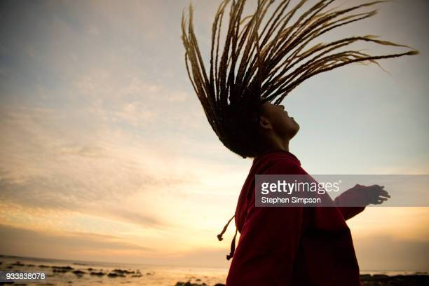 Girl flipping hair through air at sunset