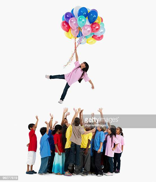 Girl floating away with balloons
