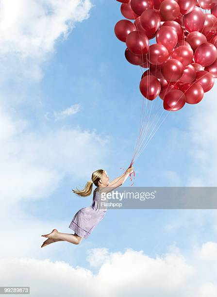 Girl floating holding big bunch of balloons