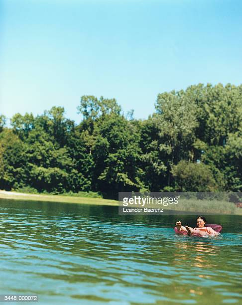 girl floating in lake - leander licht stock-fotos und bilder