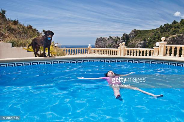 Girl (7-9) Floating in Pool with Labrador Watching