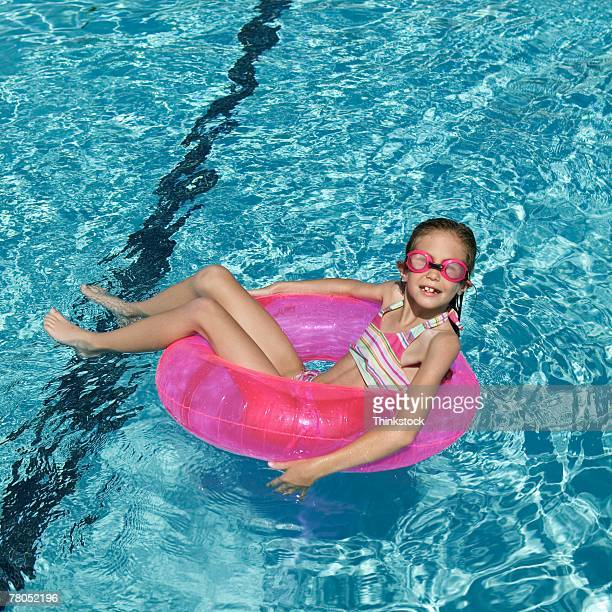 Girl floating in swimming pool