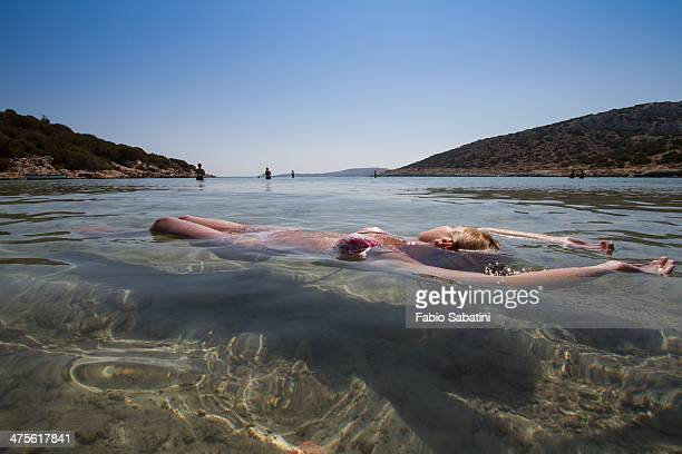 A girl floating in the water in the Greek island of Lipsi
