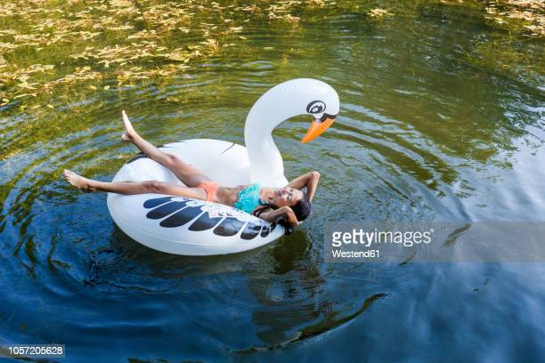 girl floating in water on inflatable pool toy in swan shape - animal representation stock pictures, royalty-free photos & images