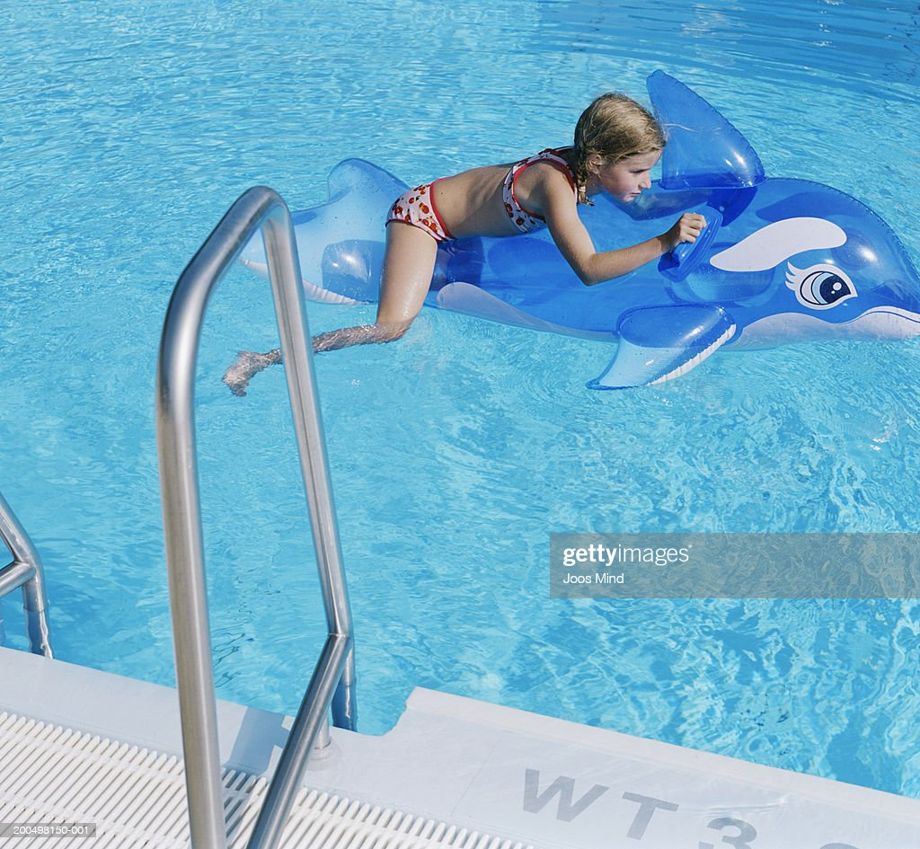 Girl Floating On Inflatable Dolphin In Swimming Pool Stock ...
