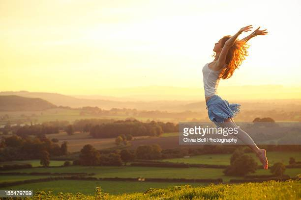 Girl Flying into air over countryside