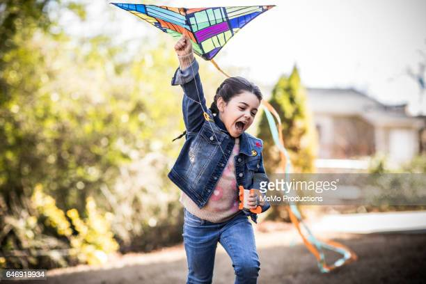 girl (7yrs) flying kite in backyard - kite toy stock pictures, royalty-free photos & images