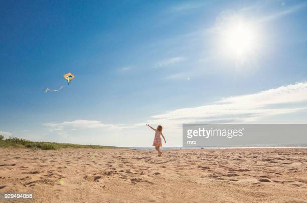 girl flying kite on beach - sandig stock-fotos und bilder
