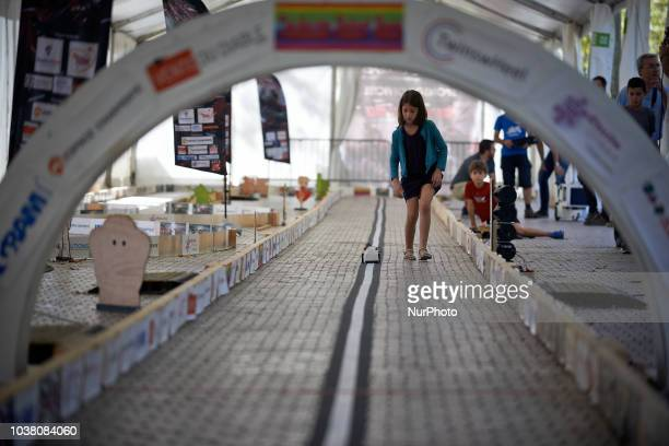 A girl foolows her robot along the track A robots race took place in Toulouse Machines are either cars or walking robots They were supposed to run a...