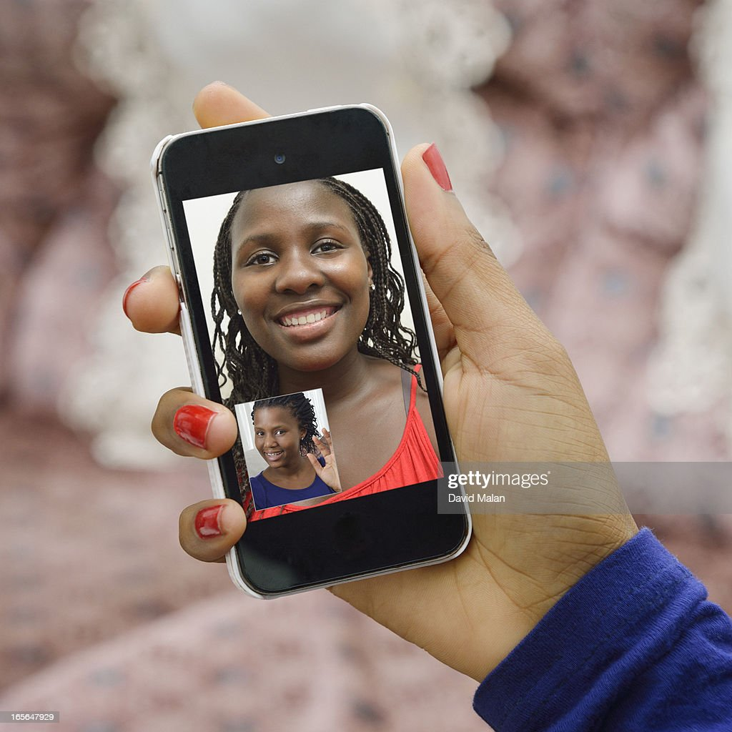 Girl friends connecting using Skype on a phone. : Stock Photo