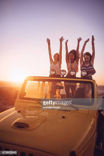 Girl friends dancing at sunset while on a road trip