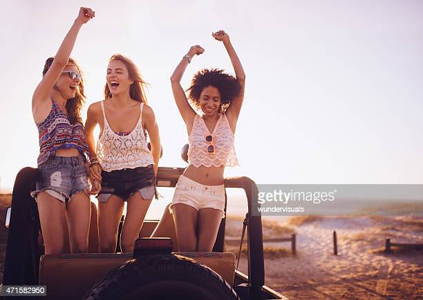 Girl friends dancing in vehicle at beach on road trip