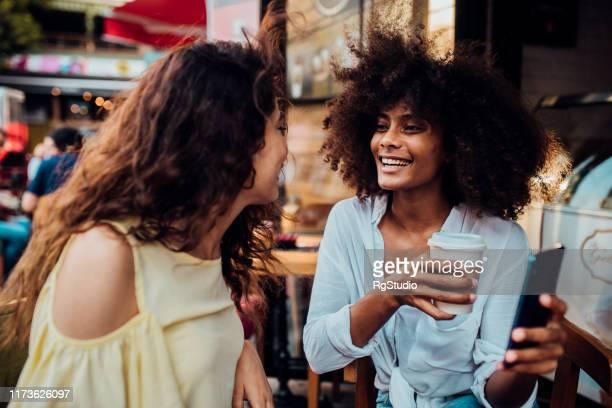 meisje vrienden drinken koffie in een koffieshop - dating stockfoto's en -beelden