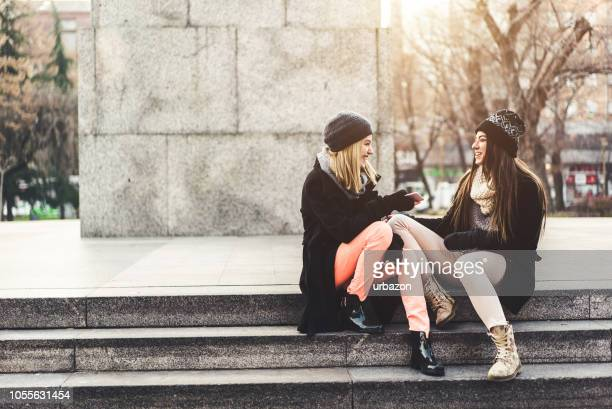 girl friends hanging out outside - pink pants stock pictures, royalty-free photos & images