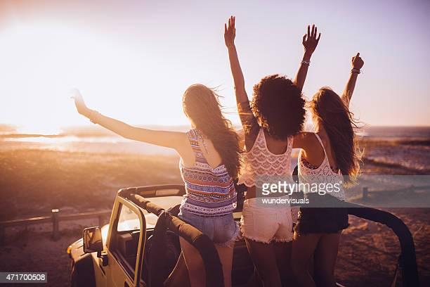 Menina amigos em uma viagem em estrada ver o pôr do sol