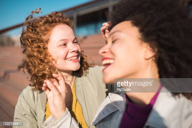 girl friends playing with hair - international womens day stock pictures, royalty-free photos & images