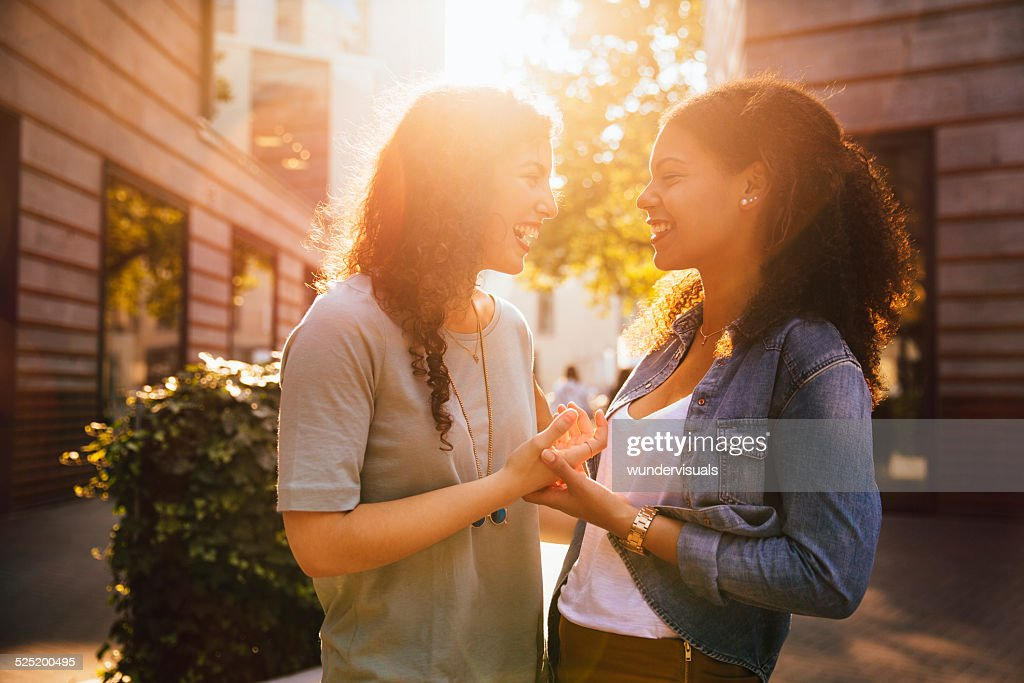 Girl Friends Reunite And Laugh Together In city : Stock Photo