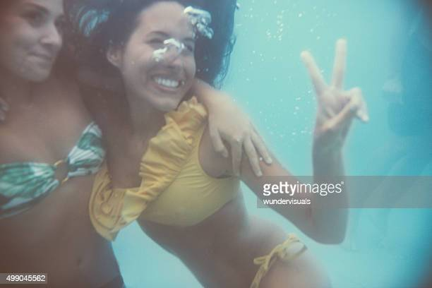Girl friends smiling and posing happily underwater in bikinis