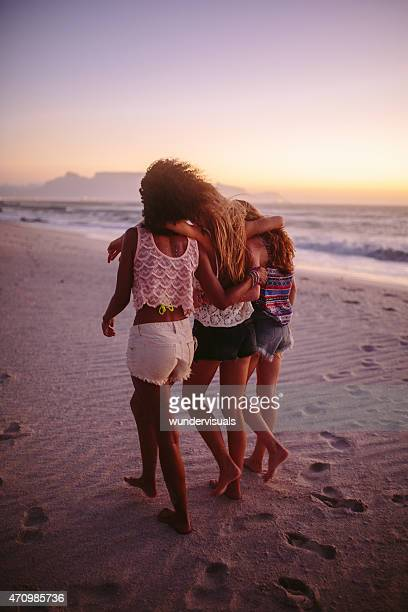 Girl friends walking together on the beach after sunset