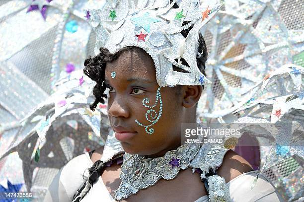 Girl from a local carnival band rests while waiting to perform during the first T20 match between West Indies and New Zealand at the Central Broward...