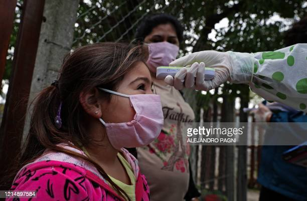Girl from Altos de San Lorenzo neighbourhood, near the city of La Plata, 65 km from Buenos Aires, has her temperature taken by a health worker on May...