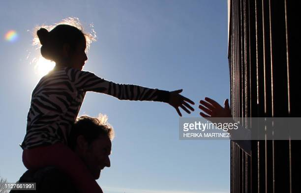 A girl from Anapra a neighbourhood on the outskirts of Ciudad Juarez in Mexico touches hands with a person on the United States through the border...
