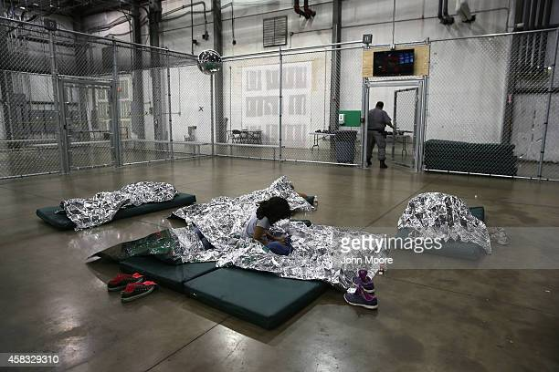 A girl from Central America rests on thermal blankets at a detention facility run by the US Border Patrol on September 8 2014 in McAllen Texas The...
