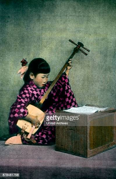 A girl from Japan plays a traditional stringed instrument the shamisen