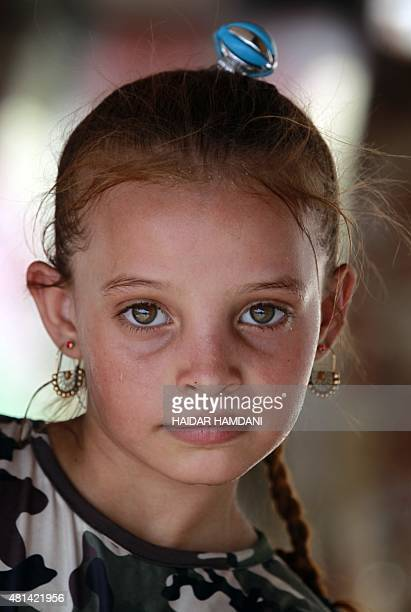 A girl from of an impoverished Iraqi family reportedly living on five dollars a day and living in structures made up of scrap metal poses for a photo...