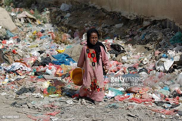 TOPSHOT A girl from the AlAkhdam community meaning 'servant' in Arabic walks amongst rubbish at a slum in the Yemeni capital Sanaa on November 9 2016...