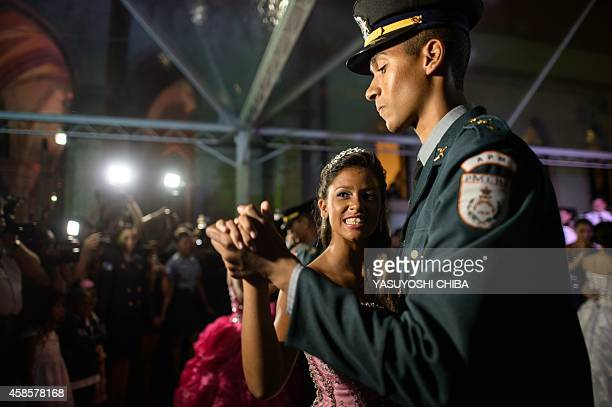A girl from the CerroCora favela who turns 15 this year dances a waltz with a police officer during her group debutante ball organized by the...