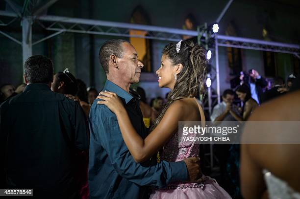 A girl from the CerroCora favela who turns 15 this year dances a waltz with her grandfather during her group debutante ball organized by the...