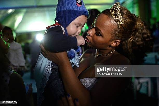 A girl from the CerroCora favela who turns 15 this year holds her son during her group debutante ball organized by the Pacifying Police Unit from...