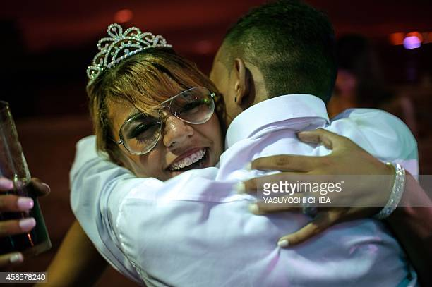 A girl from the CerroCora favela who turns 15 this year is embraced by a relative during her group debutante ball organized by the Pacifying Police...